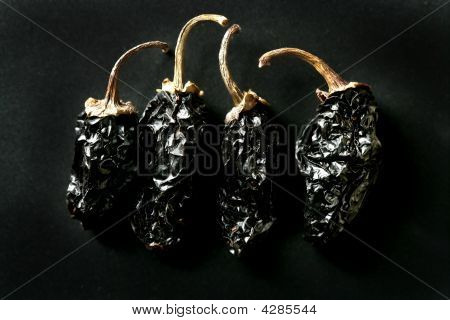 Four Black Mexican Dried Chili Peppers Black Background