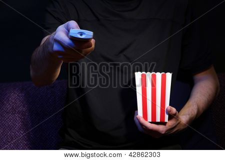 Man hand holding a TV remote control and popcorn, on dark background