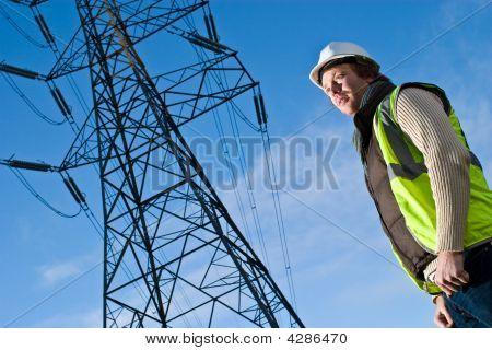 Hombre frente a una torre de electricidad