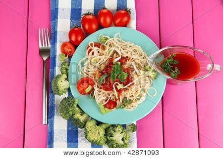 Tasty spaghetti with sauce and vegetables on plate on wooden table close-up
