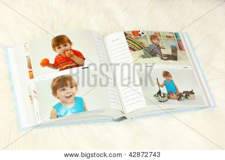 Open photo album with pictures on white carpet