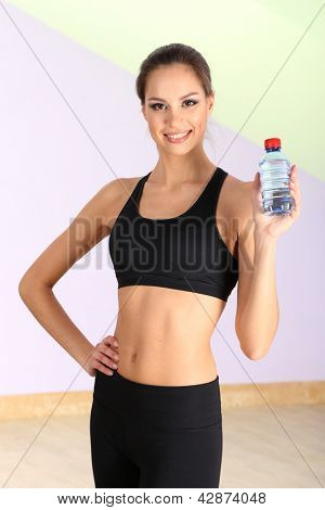 Young woman with water after workout at gym