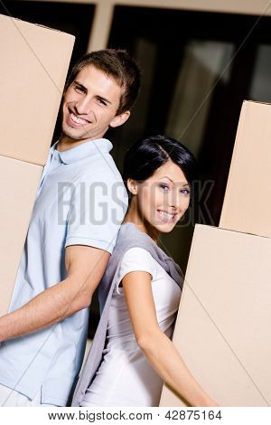 Happy couple stands back to back while carrying cardboard packages and moving to new house