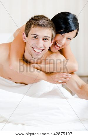 Close up of laughing couple who plays in bed-room. Woman lying on the back of the man embraces him