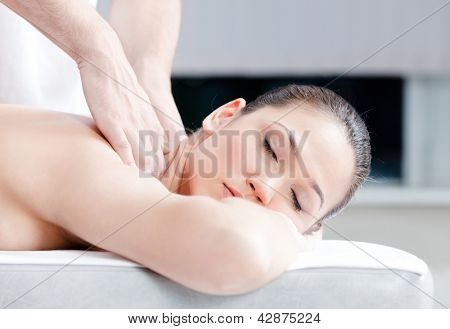 Calm woman receives body massage at spa salon