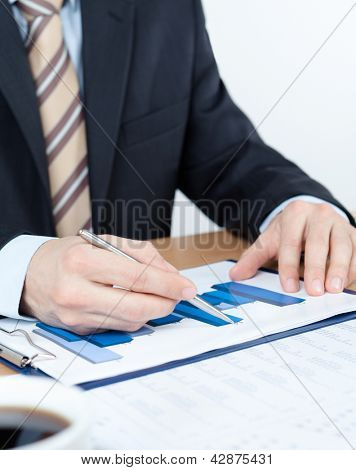 Businessman working with diagrams. Close up of hands and documents