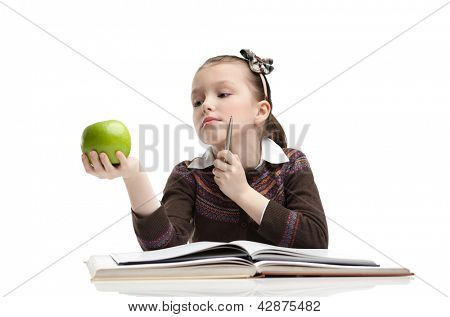 Little girl hesitates about eating a ripe green apple, isolated, white background