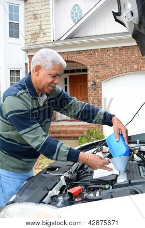 Mechanic working on a car in his driveway