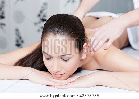 Woman gets massage therapy at spa
