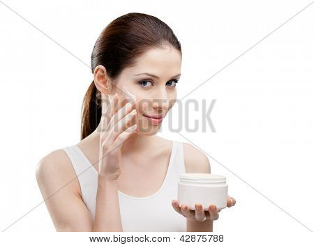 Woman applying lifting cream from container on face, isolated on white. The pursuit of beauty