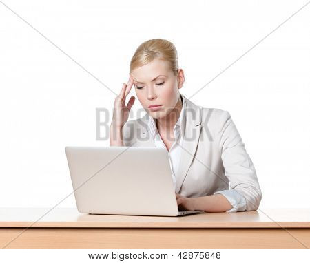 Tired young businesswoman sitting at a table with laptop, isolated