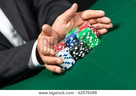 "Gambler stakes ""all in"" pushing his chips forward. Risky entertainment of gambling"