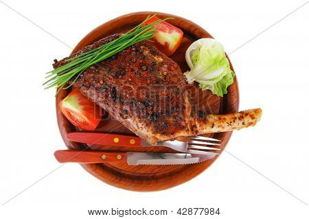 meat savory on wooden plate: roast shoulder with tomato and chives isolated on white background