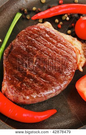 savory : grilled juicy beef steak served with hot cayenne peppers cherry tomato green chives on metal pan isolated over white background