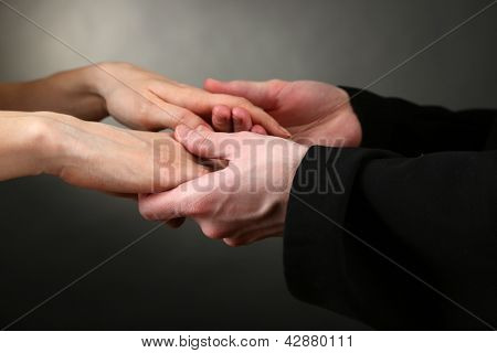 Priest holding woman hands, on black background