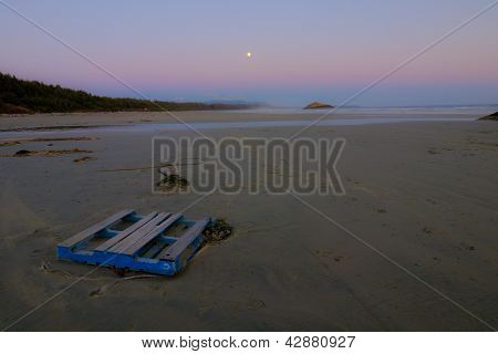 Strand in der Abenddämmerung mit Mond