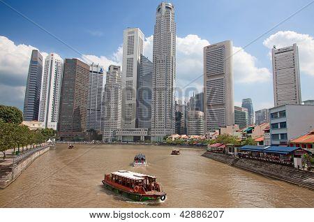 SINGAPORE - FEBRUARY 22: A tourist boat cruising Singapore river, on February 22, 2013 in Singapore. The Singapore River Cruise is a tourist attraction in this former British colony.
