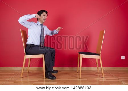 Angry businessman sited next to an empty chair