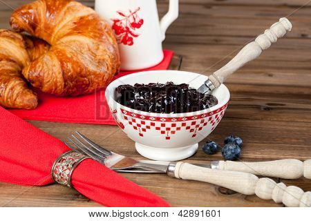 Wooden table with croissants, red napkins and antique silver napkin ring