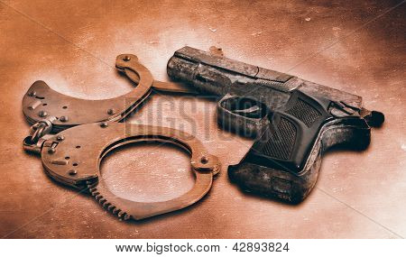 Gun And Handcuffs On Table. Photo In Old Color Image Style