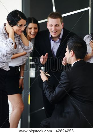 Young man romantically proposing to girlfriend offering engagement ring at working place in front of friends and colleagues