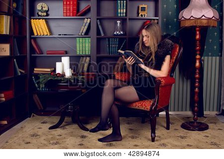 Clever young woman sits on couch and reads book at home.