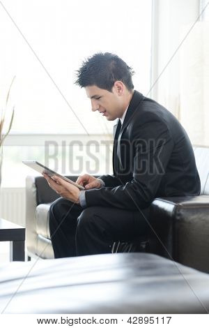 Young businessman sitting on sofa and working on tablet computer