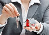 stock photo of possess  - Real estate agent with house model and keys - JPG
