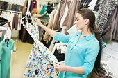 stock photo of apparel  - Young woman choosing dress during clothing shopping at apparel store - JPG