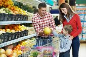 foto of supermarket  - woman with man and child choosing melon fruit during shopping at vegetable supermarket - JPG