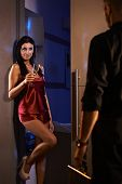 Sexy woman standing in bedroom door in red silk pyjamas, greeting man arriving from work.