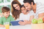 stock photo of fruit bowl  - Family using a tablet pc in kitchen - JPG