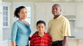 African American Family Stands In Kitchen Staring