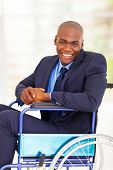 foto of handicapped  - optimistic handicapped african businessman sitting on wheelchair - JPG