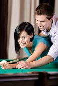 Man teaching young woman to play billiards. Spending free time on gambling