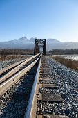 image of trestle bridge  - Narrow railroad bridge spans river in Alaska - JPG