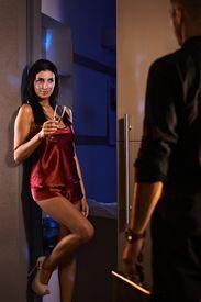 stock photo of pyjama  - Sexy woman standing in bedroom door in red silk pyjamas - JPG