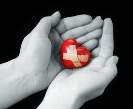 picture of broken-heart  - female hands with broken heart on black - JPG