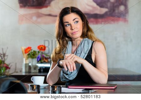 Young woman in a cafe or restaurant, she looking at the watch and is impatiently waiting for on someone who is delayed
