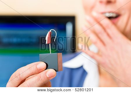 Older woman or female pensioner with a hearing problem make a hearing test, she holding a model of a hearing aid