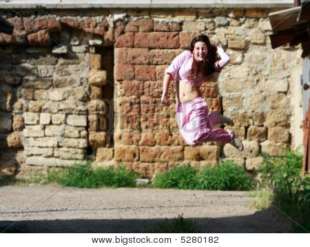 Happy Girl Jumping On Grunge Background