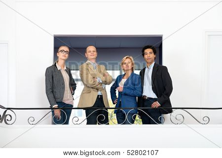 Friendly looking managment team, posing on an indoor balcony lobby.