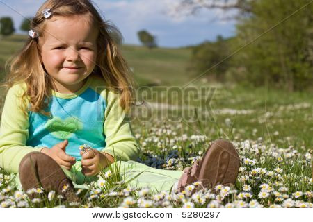 Little Girl Sitting Among Wildflowers On The Field