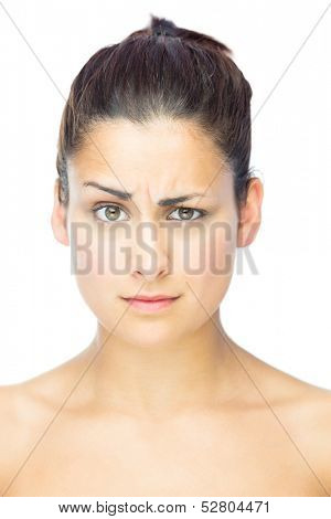 Front view of skeptical woman looking at camera on white background