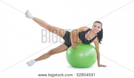 Content active woman doing an exercise on a green fitness ball smiling at camera