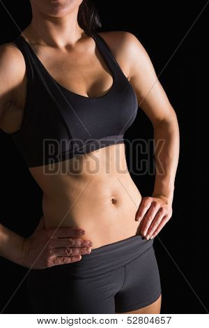 Mid section of slender fit woman posing in sportswear on black background