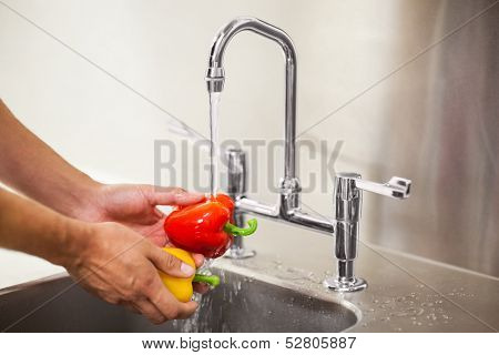 Kitchen porter washing vegetable in professional kitchen