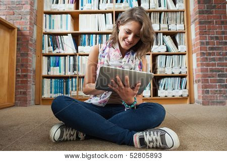 Full length of a happy female student against bookshelf using tablet PC on the library floor