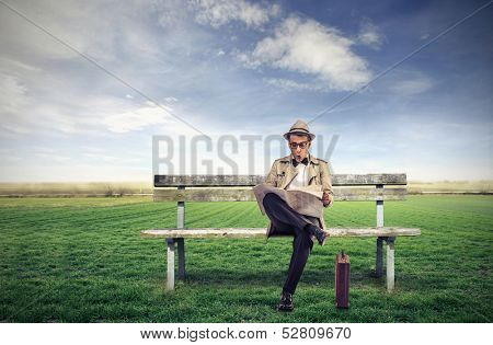 young man reading a newspaper sitting on a bench in the countryside