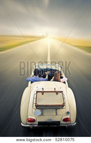 young couple traveling on a vintage car